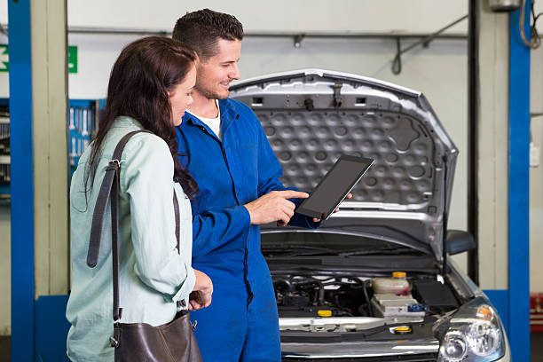 Mechanic explaining issues to customer after car service Mechanic showing customer the problem with car at the repair garage auto mechanic stock pictures, royalty-free photos & images