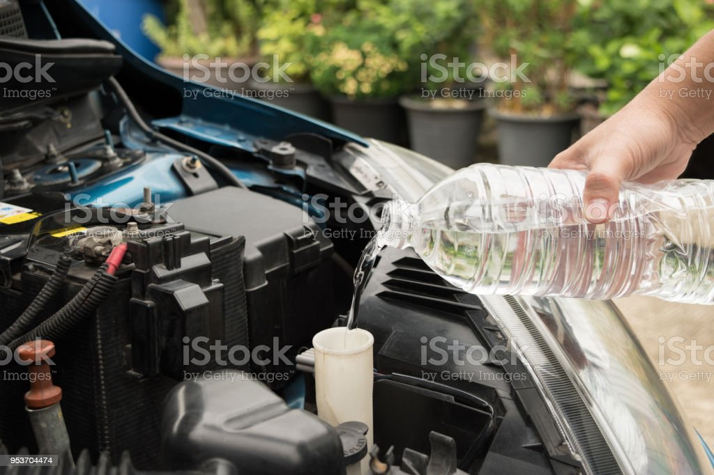 mechanic fill fresh water into windscreen or in water tank wiper on car engine room. stock photo