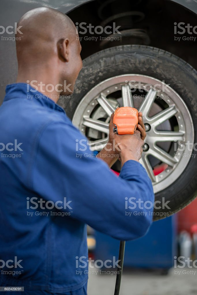 Mechanic fixing a flat tire stock photo
