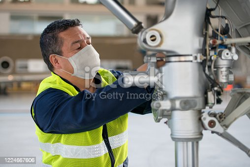 Portrait of a Latin American Mechanic fixing an airplane while wearing a facemask - Pandemic lifestyle, concepts