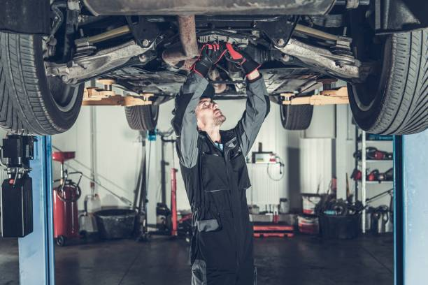 Mechanic Fixing Car on a Lift Caucasian Car Mechanic Under Vehicle Looking For Potential Issues with a Drivetrain. Automotive Industry. mechanic stock pictures, royalty-free photos & images
