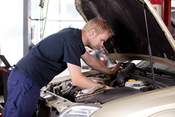 Mechanic fixing old car engine A young mechanic under the hood of a car doing repairs vehicle hood stock pictures, royalty-free photos & images