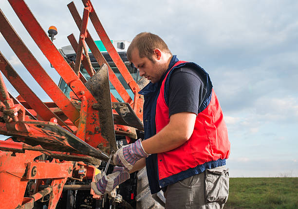 Mechanic fixing plow on the tractor Young mechanic fixing plow on the tractor agricultural equipment stock pictures, royalty-free photos & images