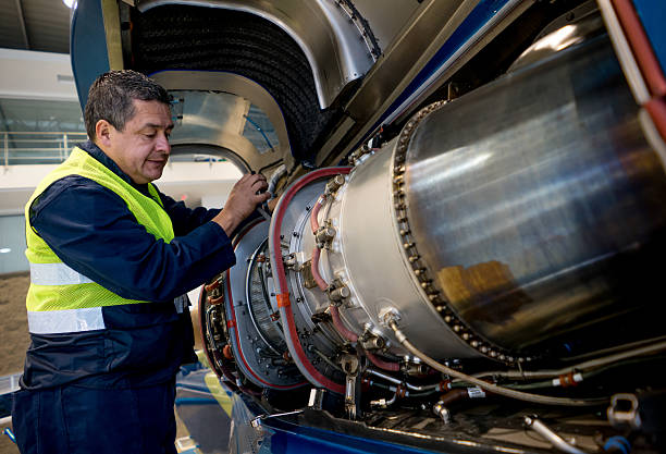Mechanic fixing the engine of an airplane stock photo