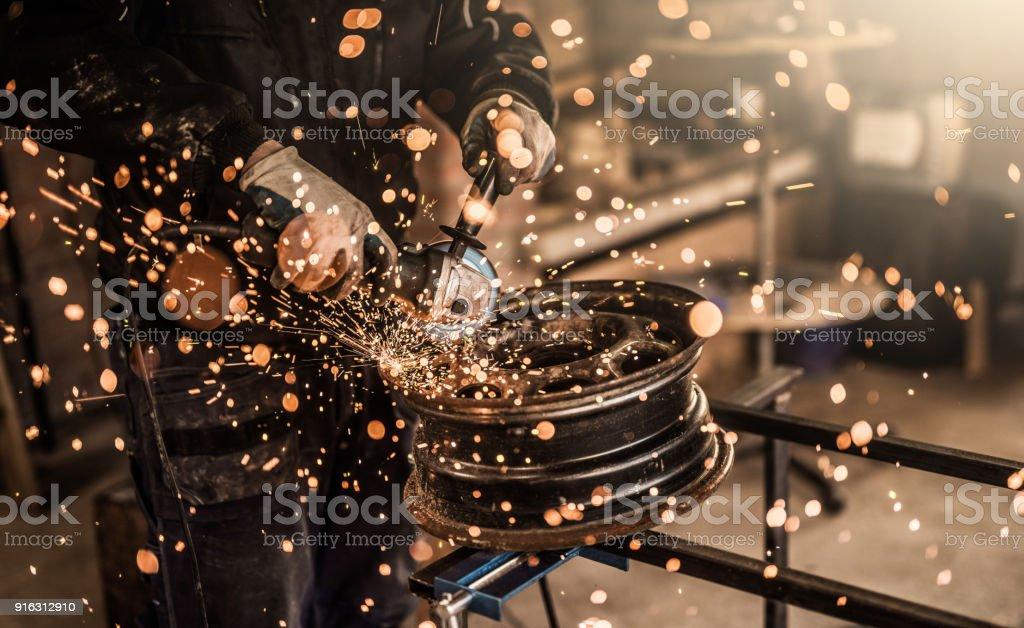 Mechanic grinding a damaged steel wheel close up. stock photo