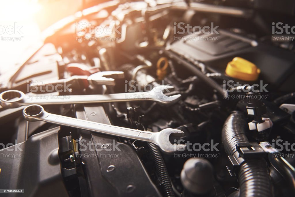 Mechanic hand checking and fixing a broken car in car service garage Mechanic hand checking and fixing a broken car in car service garage. Back Stock Photo