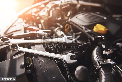istock Mechanic hand checking and fixing a broken car in car service garage 879696440
