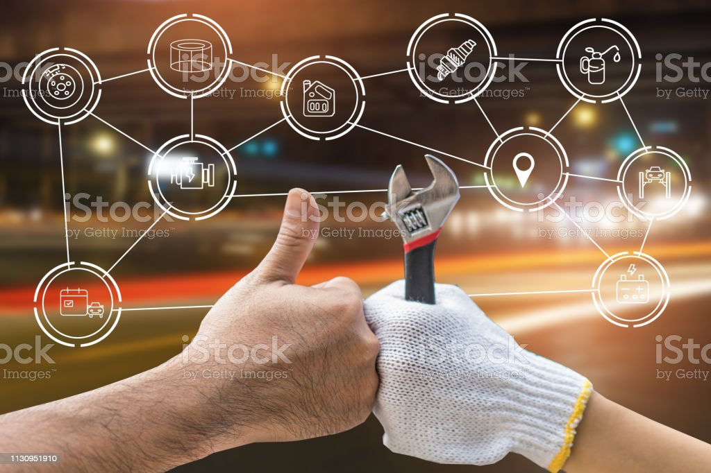 Mechanic hand checking and fixing a broken car in garage.hand of...
