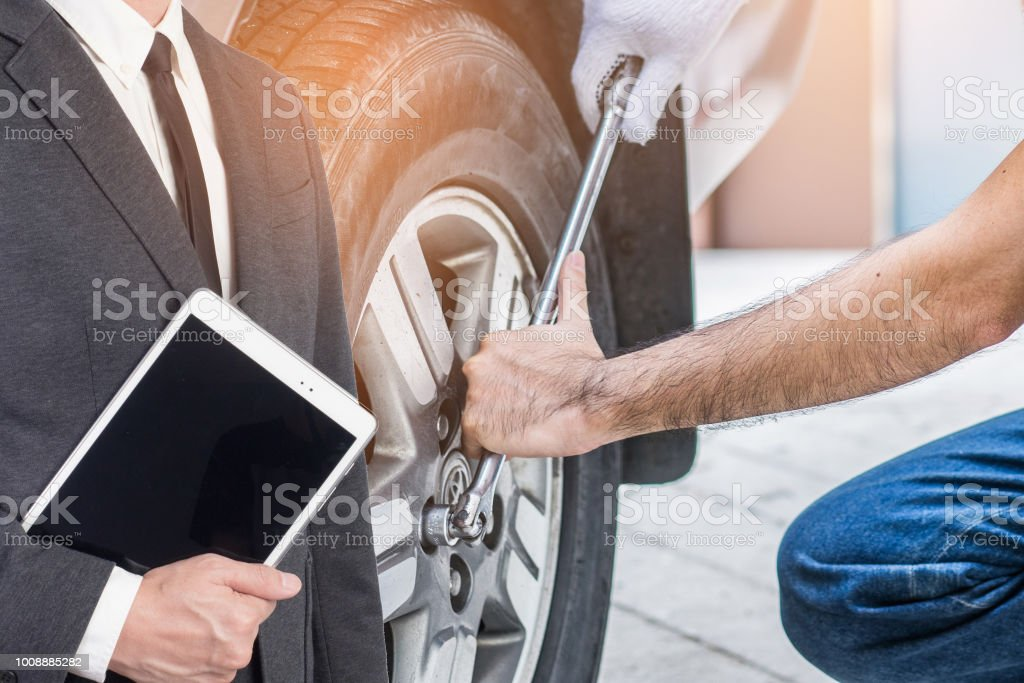 Mechanic hand checking and fixing a broken car in garage.Inspector...
