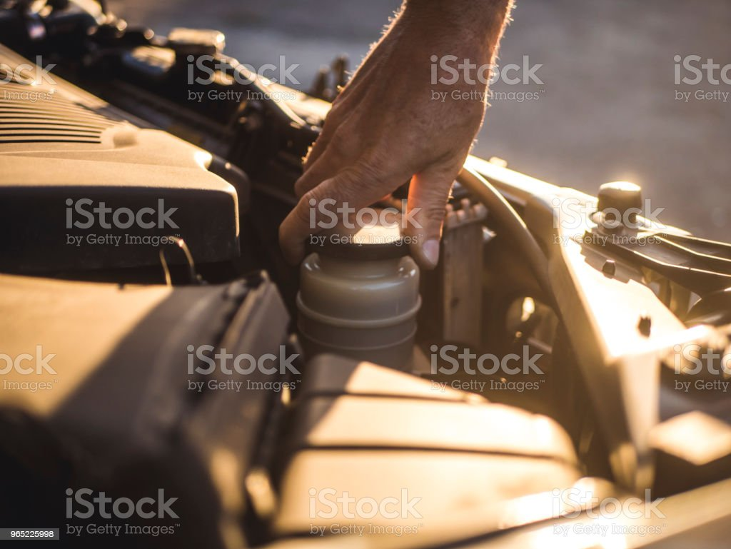 mechanic hand repairing the car with opened hood royalty-free stock photo