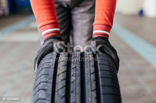 Closeup of mechanic hands holding a black tire in the workshop
