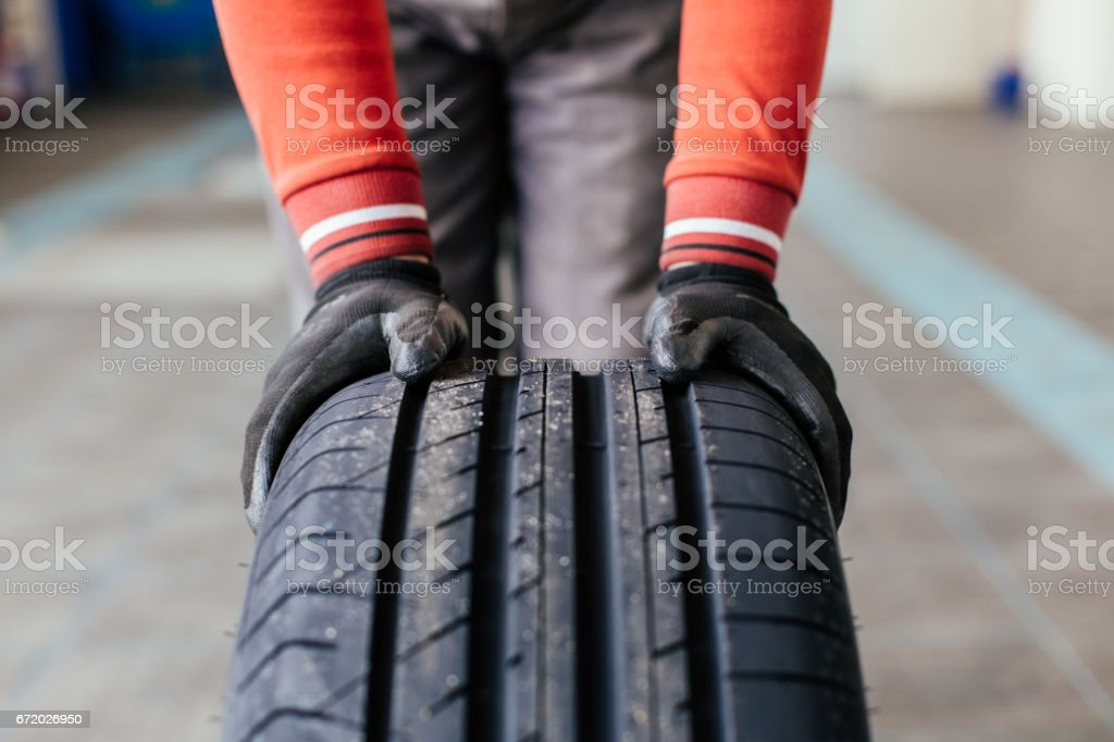 mechanic hands pushing a black tire – Foto