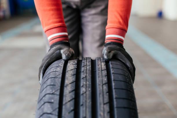 mechanische handen die een zwarte band duwen - tyre stockfoto's en -beelden
