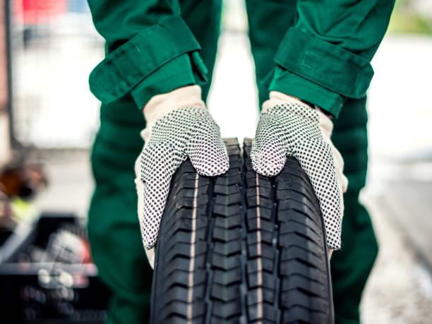 mani meccaniche che spingono lo pneumatico - transport truck tyres foto e immagini stock