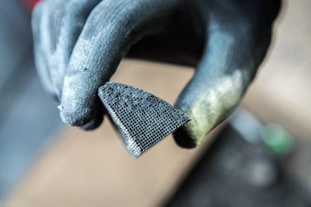mechaniker hält einen pice gebrochen katalysator - adapter stock-fotos und bilder