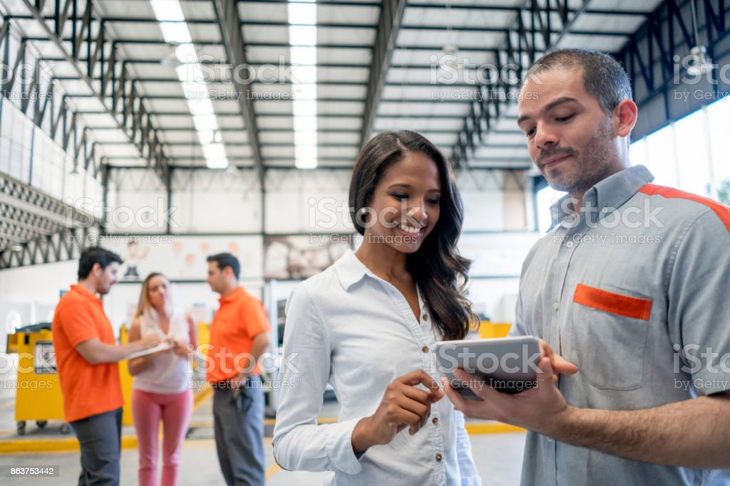 Mechanic holding a tablet computer talking to a woman about her car at a garage - lifestyle concepts stock photo