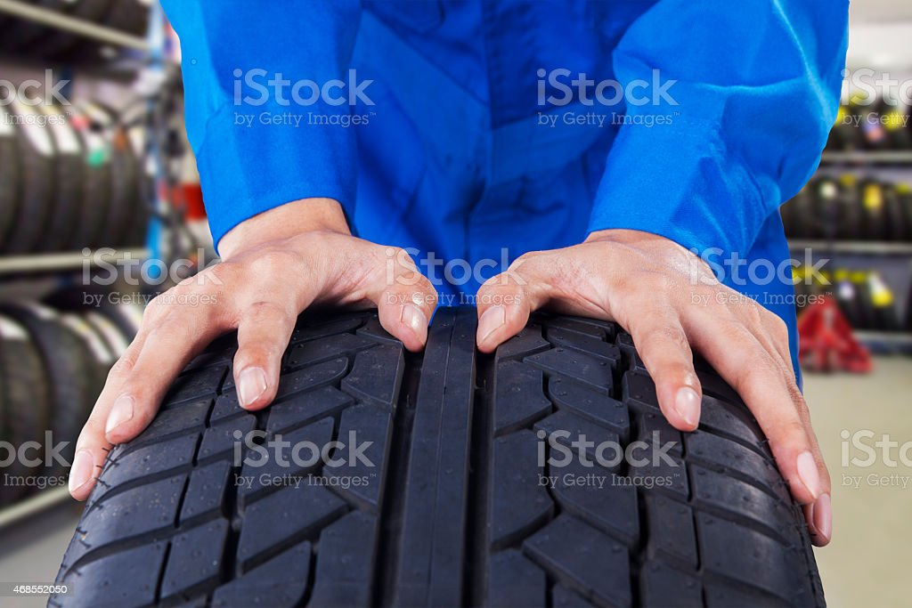 Mechanic holding a tire in vehicle shop stock photo