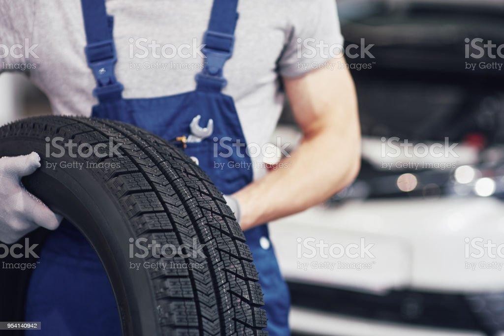 Mechaniker hält einen Reifen Reifen in der Werkstatt. Ersatz von Winter und Sommer Reifen – Foto