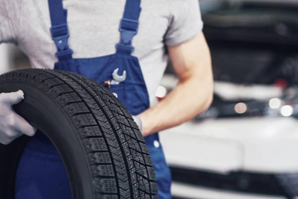 monteur houdt een band moe bij de garage voor reparatie. vervanging van de winter en zomer banden - autoband stockfoto's en -beelden