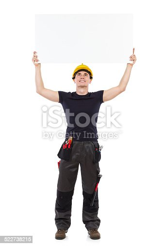 istock Mechanic holding banner above his head. 522738215