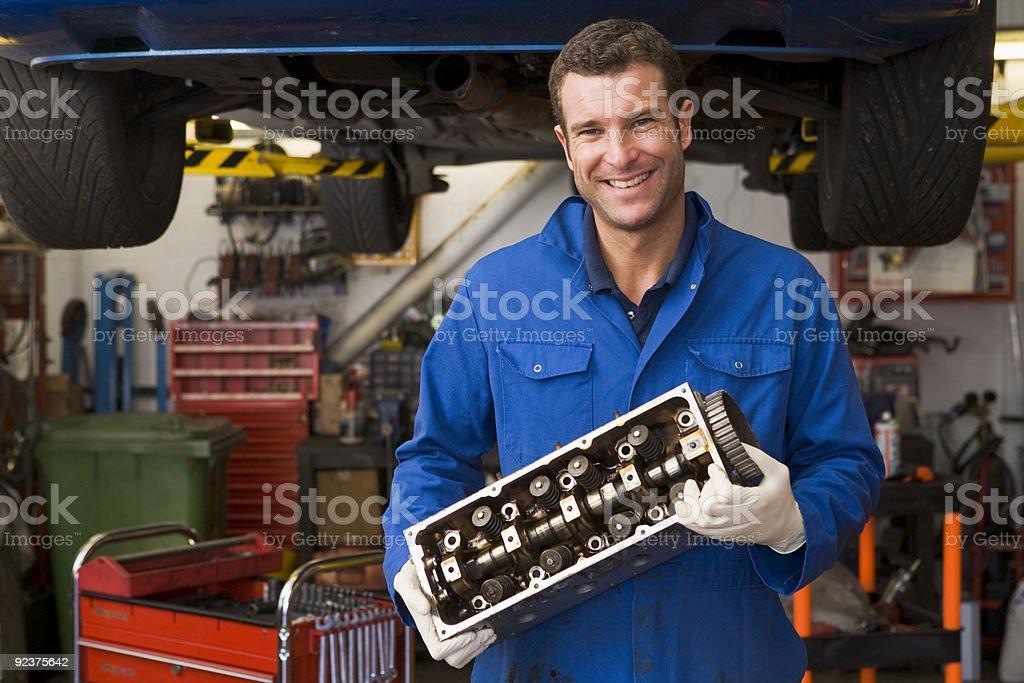 Mechanic holding car part royalty-free stock photo