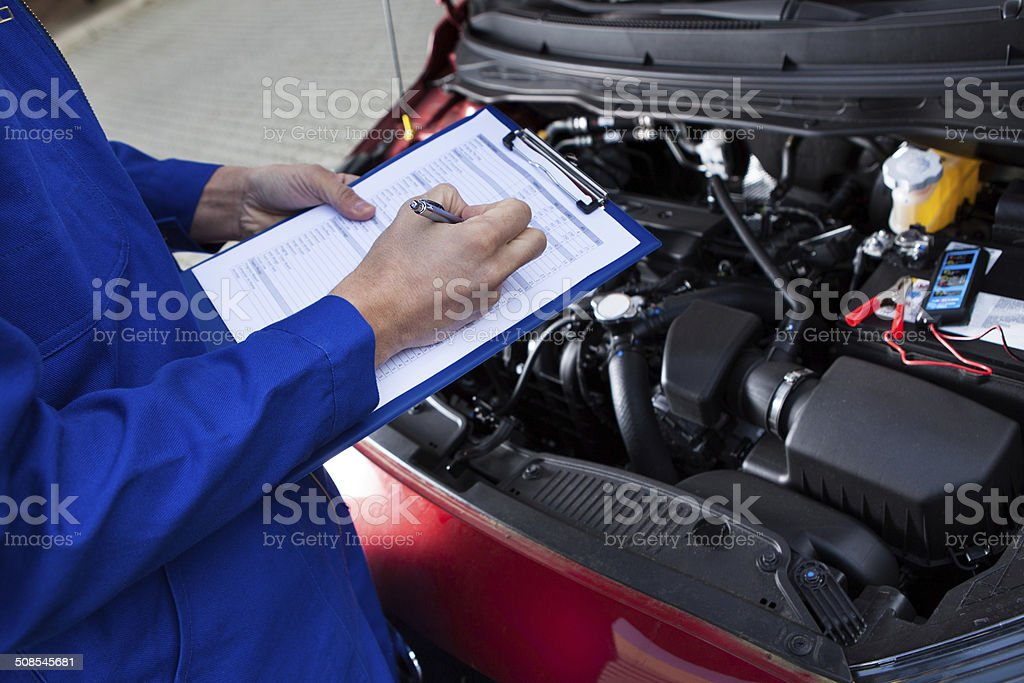 Mechanic Holding Clipboard In Front Of Open Car Engine stock photo