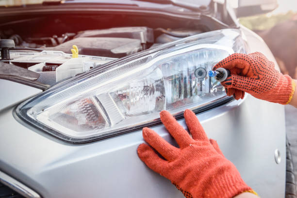 Mechanic holding lamp and cables from headlamp of car Mechanic holding lamp and cables from headlamp of car headlight stock pictures, royalty-free photos & images