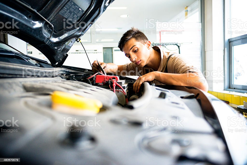 Mechanic in auto repair shop working on car stock photo