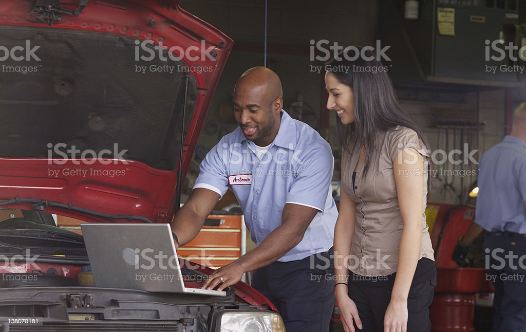 Mechanic in auto shop helping customer stock photo