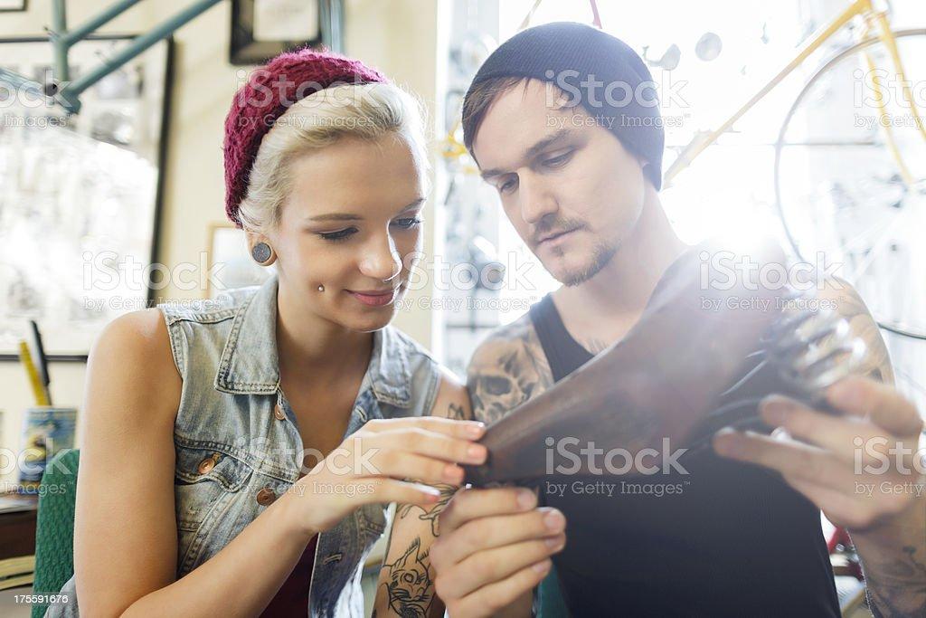 Mechanic in Berlin showing his customer an antique bike seat stock photo