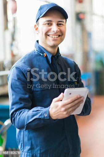 istock Mechanic in blue clothing using a tablet at work 468190578