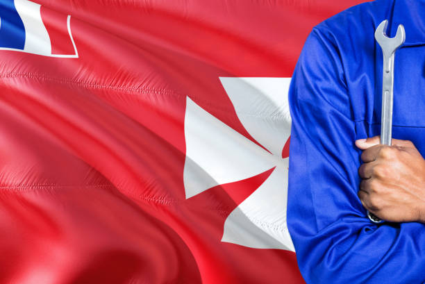 Mechanic in blue uniform is holding wrench against waving Wallis And Futuna flag background. Crossed arms technician. stock photo