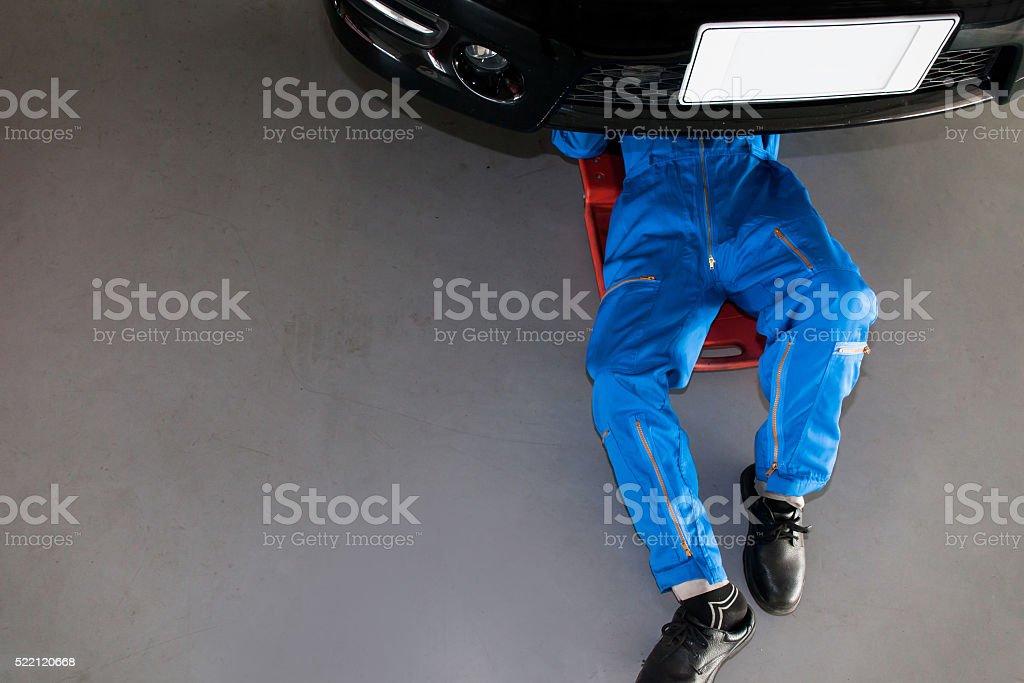 Mecánico en azul uniforme acostarse y trabajo en automóvil - foto de stock