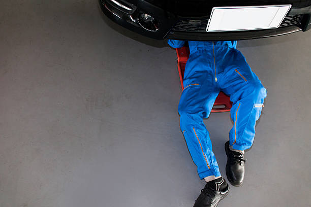 Mechanic in blue uniform lying down and working under car stock photo