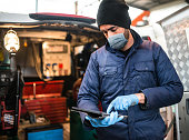 istock mechanic in front of the van with face mask 1222853907