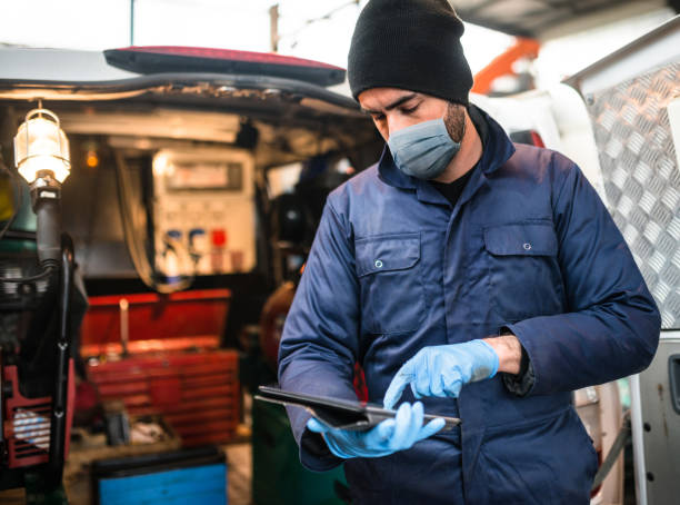 mechanic in front of the van with face mask stock photo