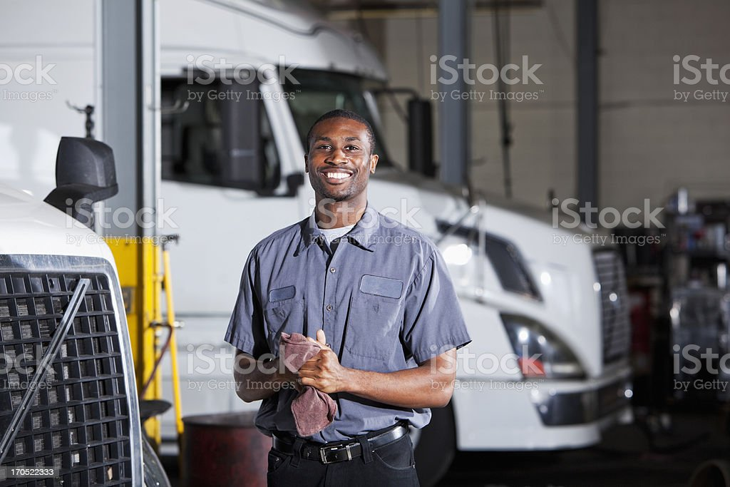 Mechanic in garage with semi-truck stock photo