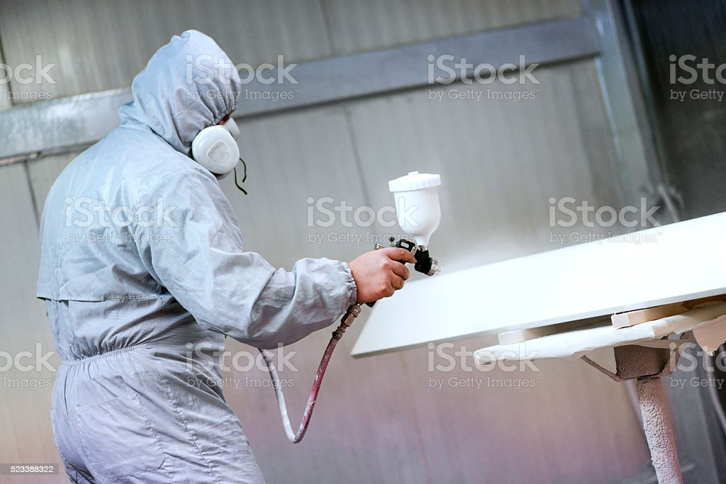 Mechanic in Painting Booth Spray Wooden Part of Furniture stock photo
