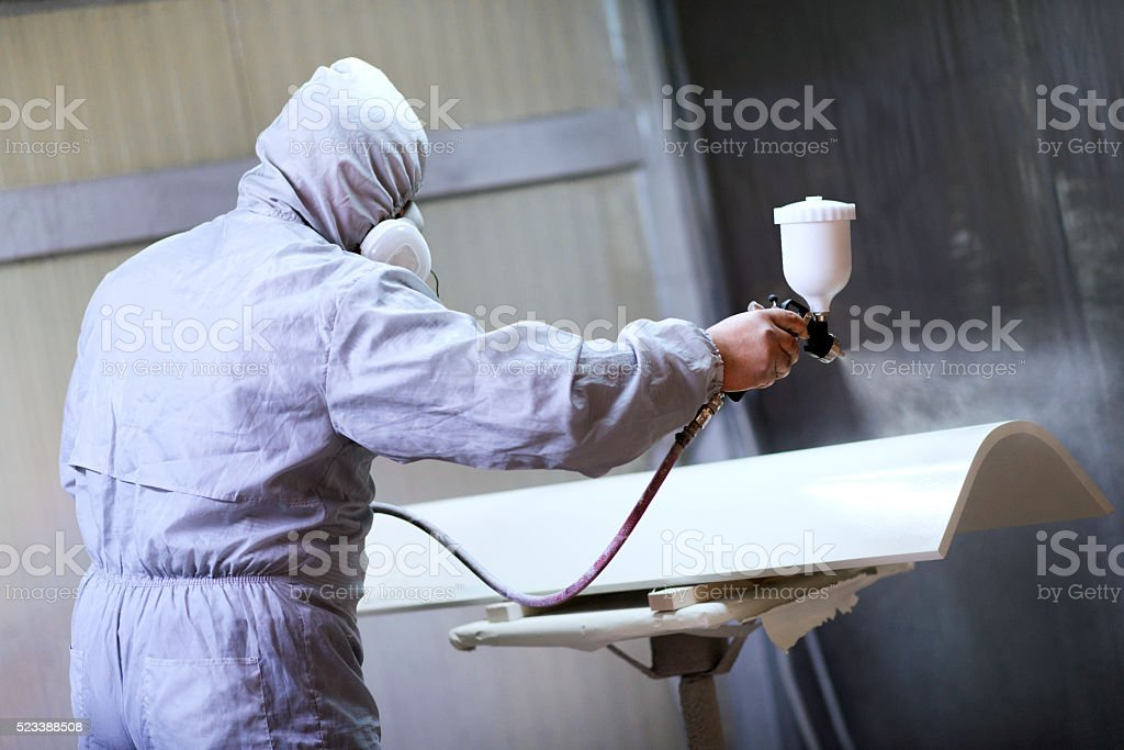 Mechanic in Painting Booth Spray Wooden Part of Furniture or hood of...
