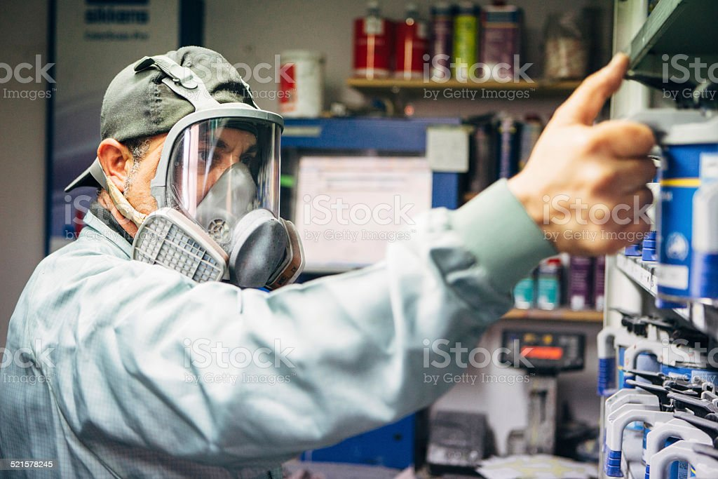 mechanic in protective workwear chooses colors for airbrush stock photo