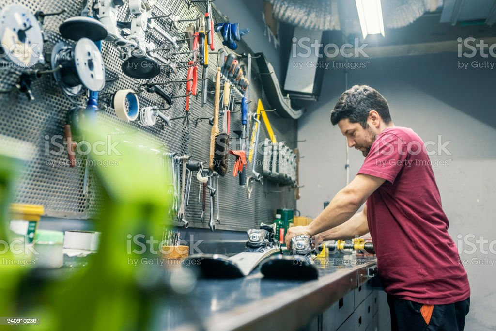 Mechanic in Ski repair shop stock photo