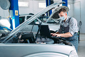 istock Mechanic in uniform and protective mask work in a car workshop. 1269258353