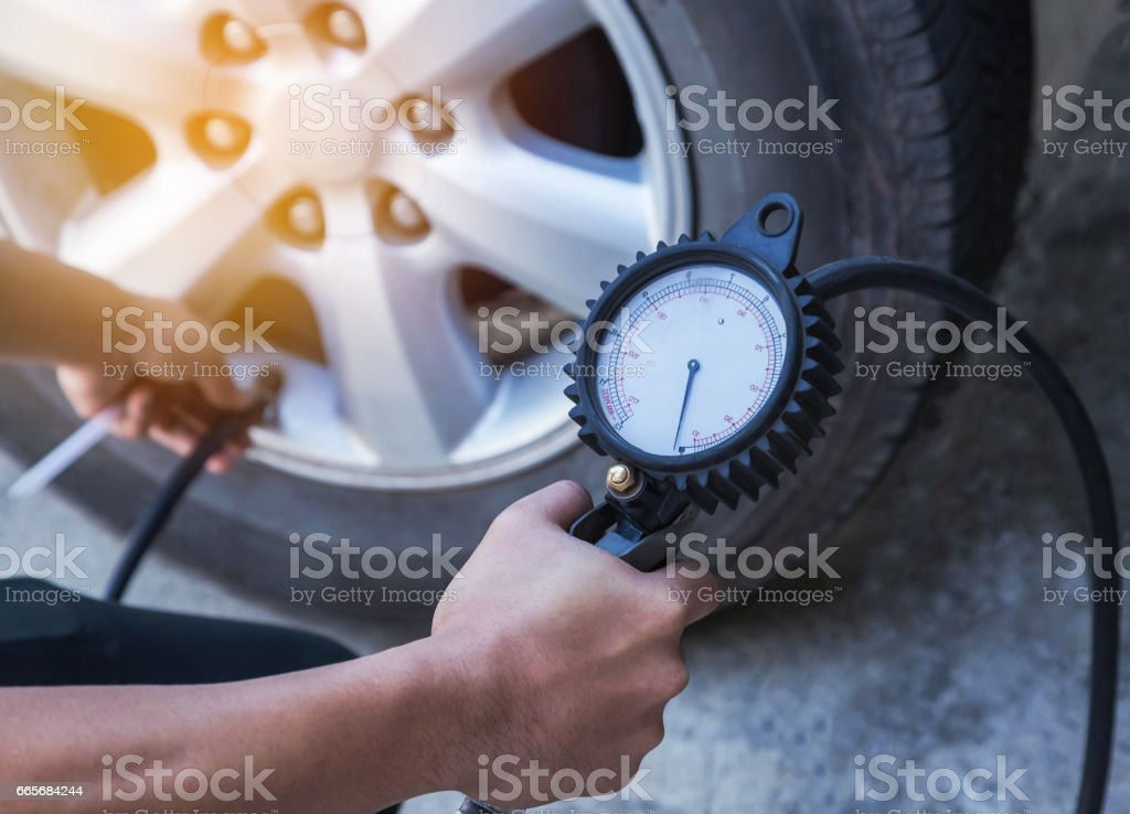 mechanic inflating tire and checking air pressure with gauge pressure stock photo