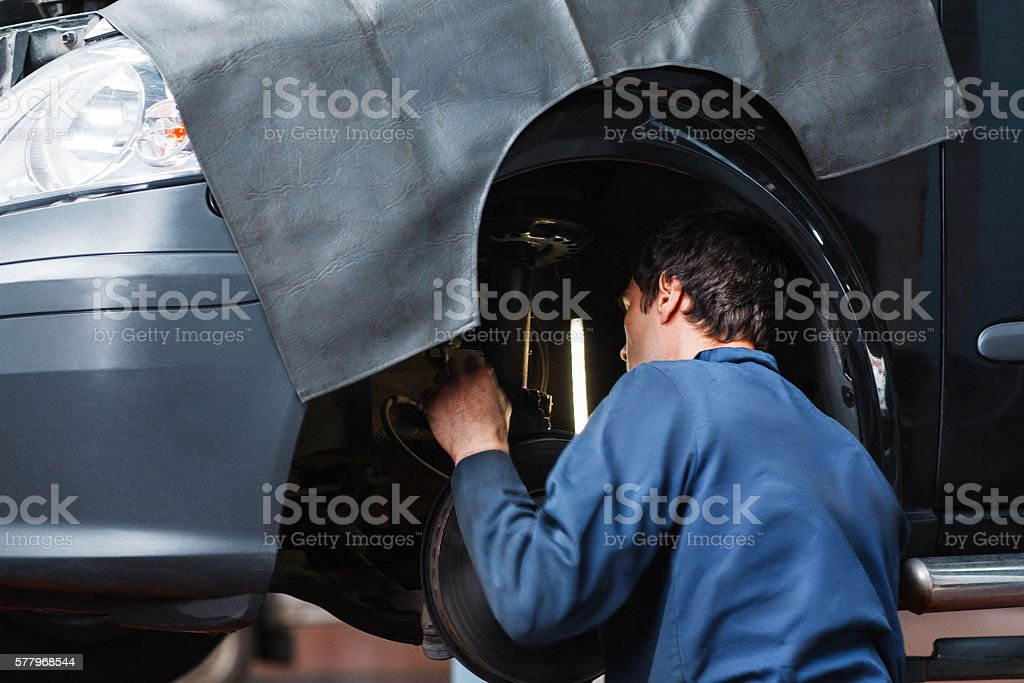 Mechanic inspecting car suspension system stock photo