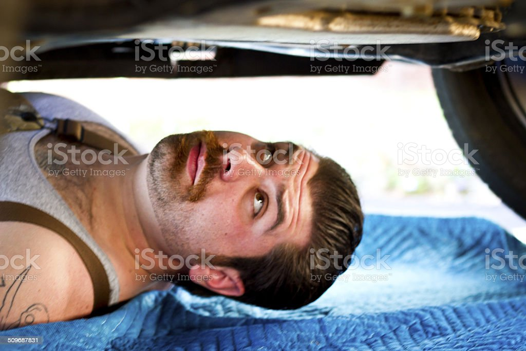 Mechanic inspecting underside of car stock photo
