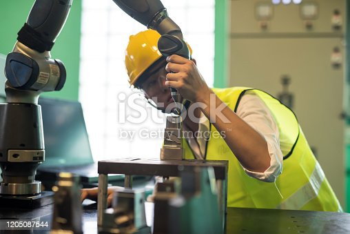 1142508104 istock photo mechanic inspector check automate robot in factory 1205087544