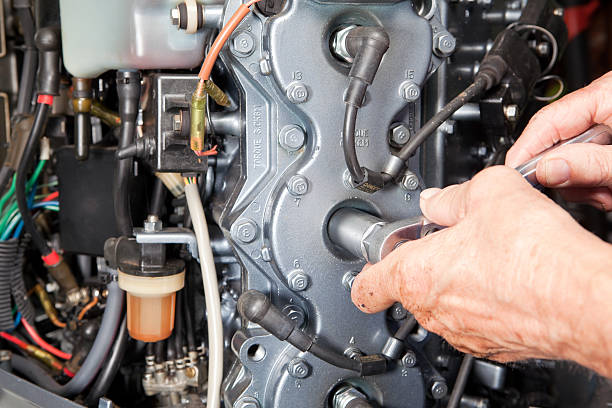 Mechanic Installing or Removing Spark Plug with Socket Wrench