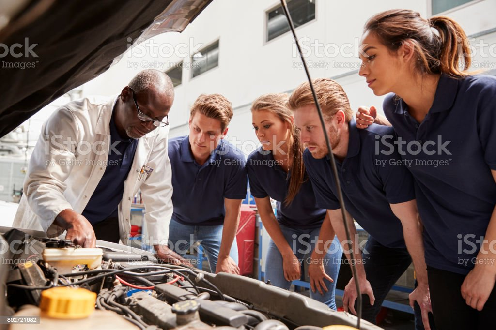 Mechanic instructing trainees around a car engine, low angle stock photo