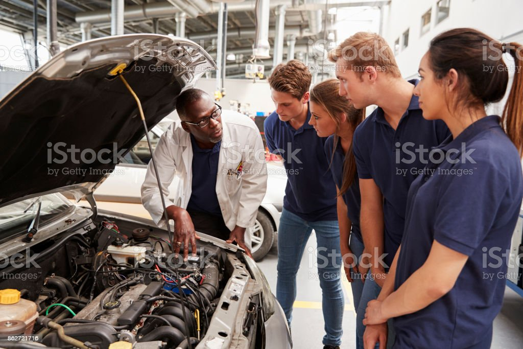 Mechanic instructing trainees around the engine of a car stock photo