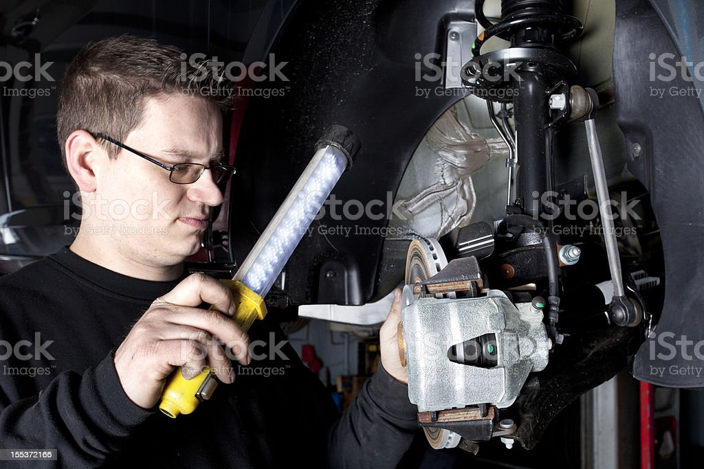 Mechanic is checking the disc brakes of a modern car stock photo